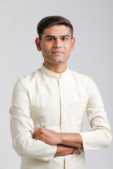 Indyjski mężczyzna w etnicznej odzieży i pozycja nad bielem