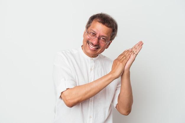 Indyjski mężczyzna w średnim wieku na białym tle czuje się energiczny i wygodny, zacierając ręce pewnie.