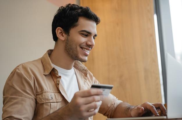 Indyjski mężczyzna za pomocą komputera przenośnego, trzymając kartę kredytową, zakupy online