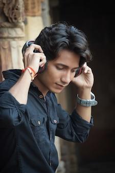Indyjski młody przystojny chłopak słucha piosenki w słuchawkach na zewnątrz