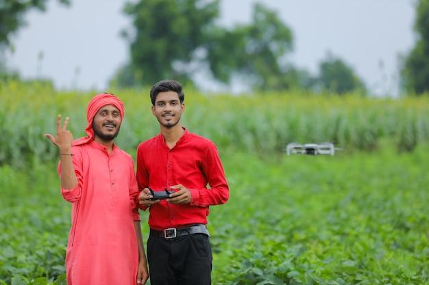 Indyjski rolnik i agronom używający drona w rolnictwie