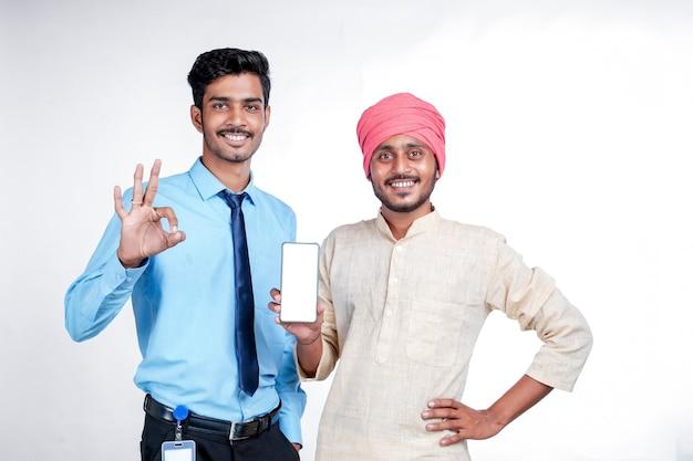 Indyjski rolnik pokazuje smartphone z oficerem na białym tle.