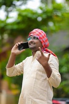 Indyjski rolnik rozmawia na smartfonie w domu.