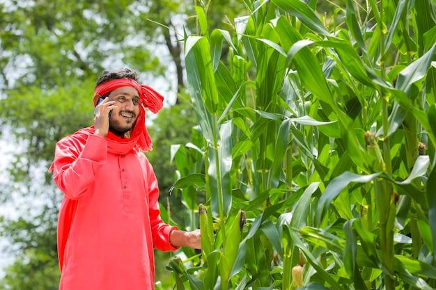 Indyjski rolnik rozmawia na smartfonie w zielonym polu kukurydzy