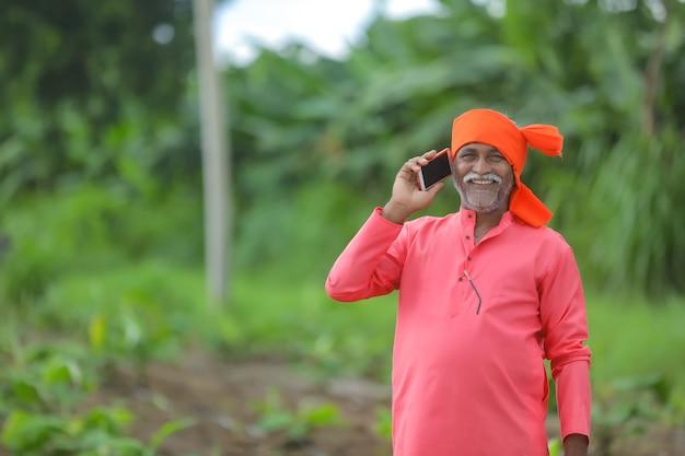 Indyjski rolnik rozmawia przez telefon komórkowy w dziedzinie rolnictwa