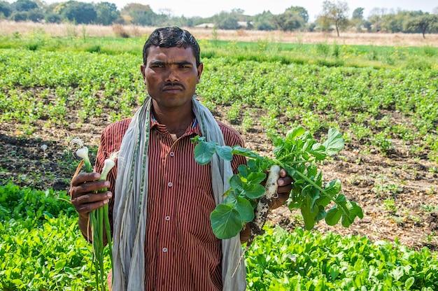 Indyjski rolnik, trzymając w rękach rzodkiewka i cebula w gospodarstwie ekologicznym