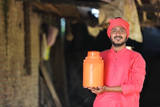 Indyjski rolnik, trzymając w ręku butelkę mleka na farmie mlecznej