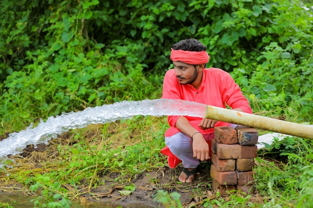 Indyjski rolnik z przepływu wody z rury w polu