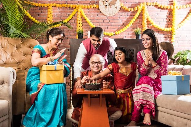 Indyjski staruszek z rodziną świętuje urodziny, dmuchając świeczki na torcie, mając na sobie etniczne stroje