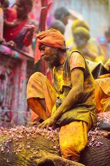Indyjski stary człowiek siedzi i cieszy się świętem holi zdjęcie premium za darmo