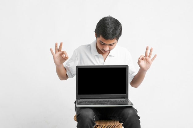 Indyjski student pokazując ekran laptopa na białej ścianie