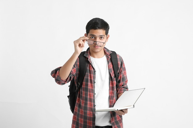 Indyjski student trzymając książki w ręku i stojąc na białej ścianie