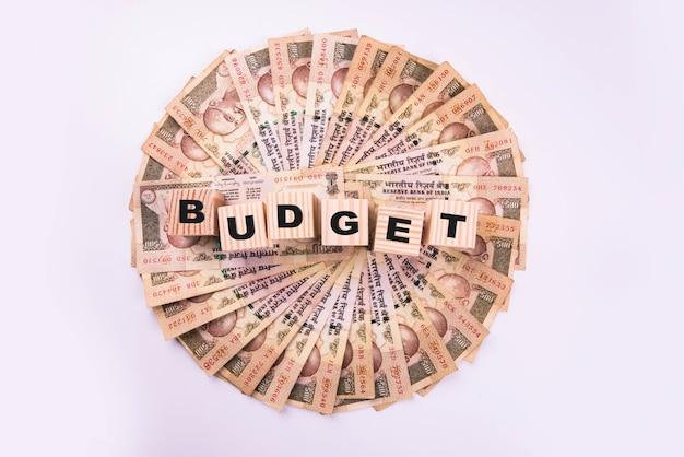 Indyjskie banknoty ułożone w okrągły kształt i tekst budżet lub oszczędność napisany na drewnianych klockach, na białym tle