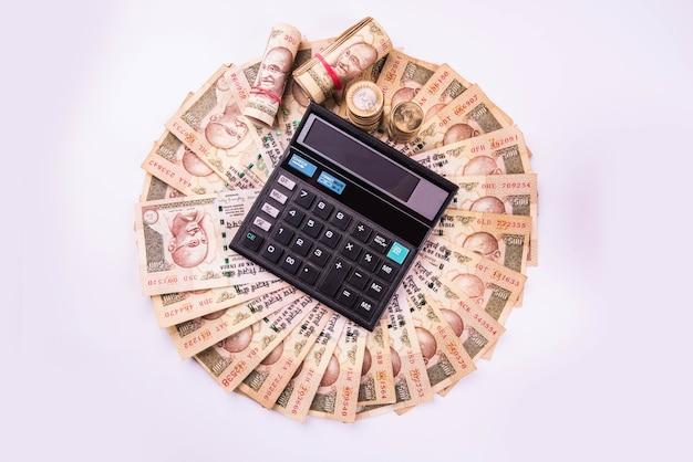 Indyjskie banknoty ułożone w okrągły kształt z kalkulatorem nad nimi