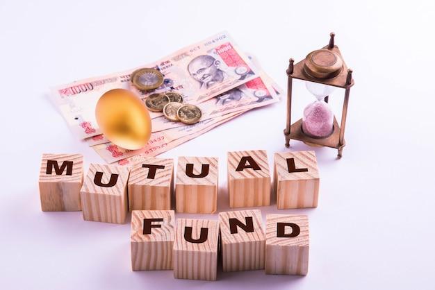 Indyjskie banknoty z monetami i złotym jajkiem wraz z zabytkowym piaskowym zegarem i drewnianymi klockami z nadpisanym środkiem wspólnym lub stałym depozytem