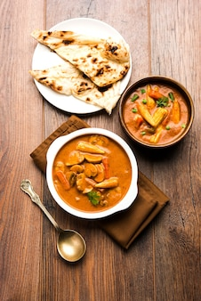 Indyjskie curry z kukurydzy i kukurydzy masala przygotowane w czerwonym sosie podawane z pieczywem roti/naan lub indyjskim. na nastrojowym tle. selektywne skupienie