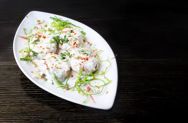 Indyjskie danie dahi bhalla na stole