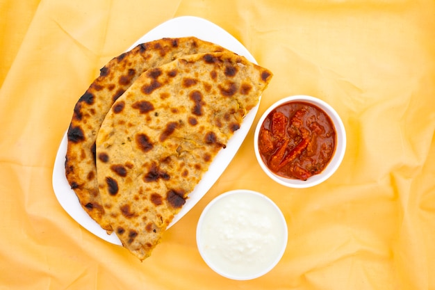 Indyjskie danie śniadaniowe aloo paratha podawane z twarogiem i marynatą