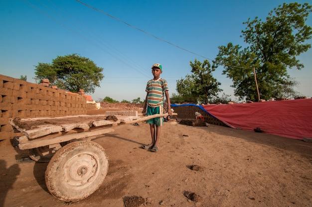 Indyjskie dzieci robotników pomagających wyrabiać tradycyjne cegły w cegielni