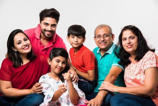 Indyjskie dzieci z rodzicami i dziadkami, siedzące na białym tle na białym tle, studio strzał