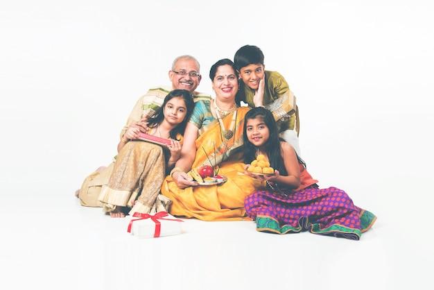 Indyjskie dzieciaki z dziadkami w tradycyjnym stroju trzymające prezenty, słodycze i puja lub pooja thali lub biorące selfie, odizolowane na białym tle