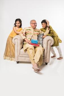 Indyjskie dzieciaki z dziadkiem siedzą na kanapie w tradycyjnych ubraniach w jakiś festiwalowy dzień dzieląc się prezentami i słodyczami