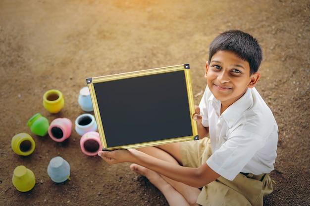 Indyjskie dziecko pisze alfabet abcd na tablicy