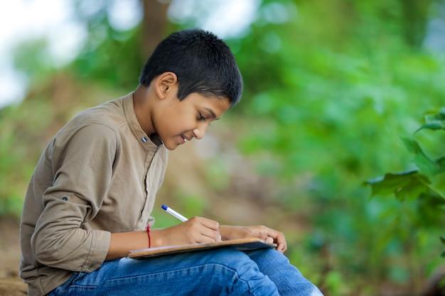 Indyjskie dziecko pisze na notatniku