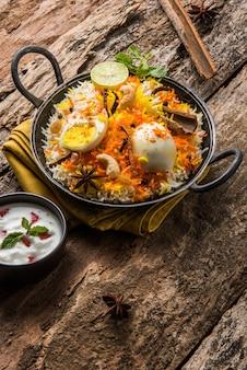 Indyjskie jajko biryani lub ryż anda podawane w kadhai lub kadai z dipem jogurtowym, selektywne focus