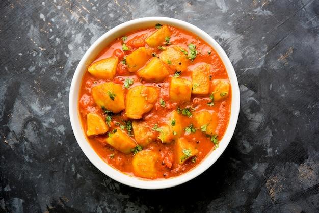 Indyjskie jedzenie - aloo curry masala. ziemniak gotowany z przyprawami i ziołami w pomidorowym curry. podawane w misce na nastrojowym tle. selektywne skupienie