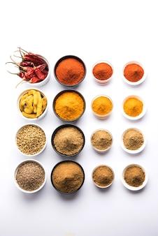 Indyjskie kolorowe przyprawy. zdjęcie grupowe czterech podstawowych indyjskich przypraw, takich jak surowe czerwone chili, kurkuma, kolendra i kminek w proszku. selektywne skupienie