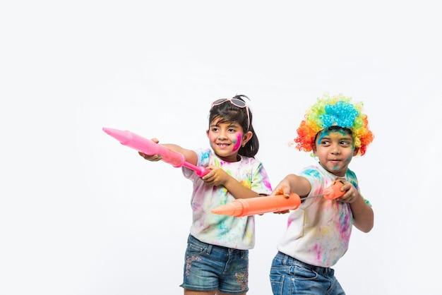 Indyjskie małe dzieci, przyjaciele lub rodzeństwo świętujące święto holi z kolorem gulal lub proszku, słodyczami, pichkari lub sprayem, odizolowane na białym tle