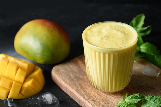 Indyjskie mango lub kurkuma lassi na czarnym tle