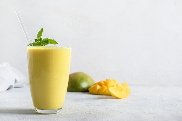 Indyjskie mango lub kurkuma lassi na szarym tle