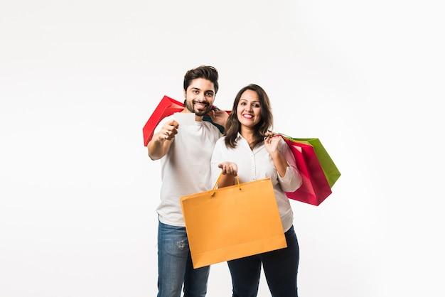 Indyjskie młode torby na zakupy para i puste karty debetowej lub kredytowej lub elektronicznej do płatności, stojąc na białym tle nad białym tłem. selektywne skupienie
