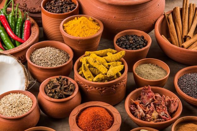 Indyjskie niezbędne przyprawy w doniczkach z terakoty ułożone na teksturowanym tle, selektywne skupienie