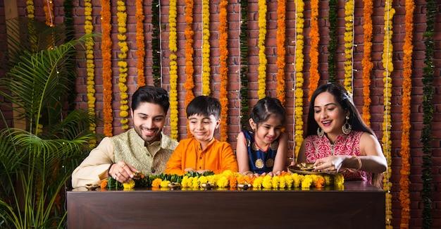 Indyjskie oświetlenie rodzinne lub aranżacja lampy naftowej lub diya wokół rangoli kwiatowego w noc festiwalu diwali