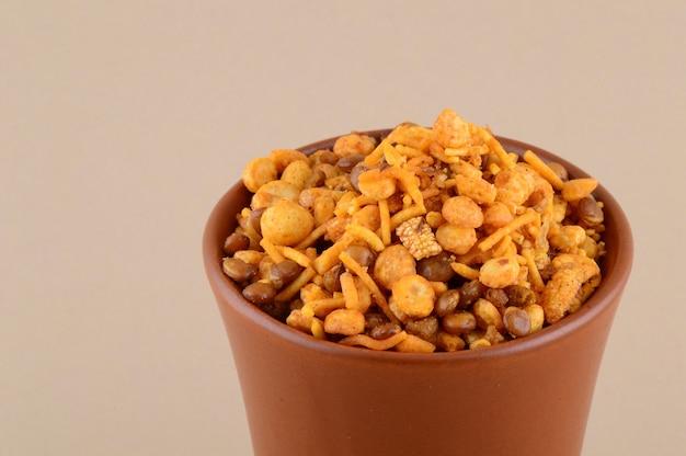 Indyjskie przekąski: mieszanka (prażone orzechy z masala solonym pieprzem, rośliny strączkowe, channa masala dal zielony groszek) w niebieskiej misce w