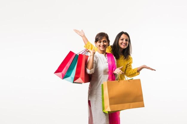 Indyjskie siostry matki córki robią zakupy z kolorowymi torbami, stojąc na białym tle nad białym tłem