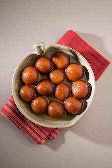 Indyjskie słodkie jedzenie gulab jamun podawane w okrągłej ceramicznej misce