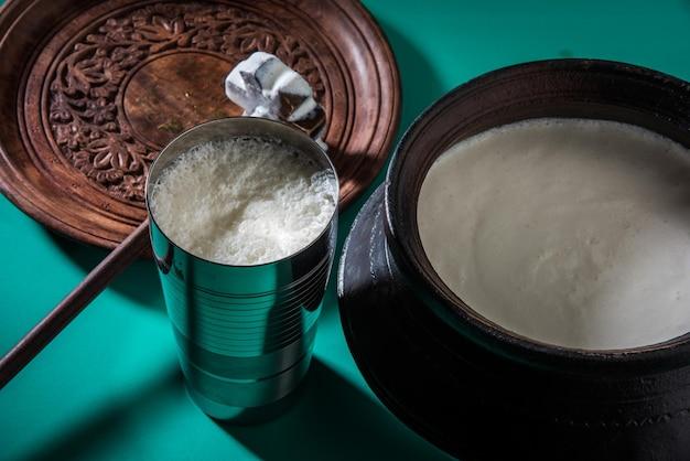 Indyjskie słodkie lassi składające się z mleka, twarogu, cukru i soli zmieszanych z kostkami lodu, podawane w jumbo stalowej szklance, przygotowane w tradycyjnym glinianym garnku