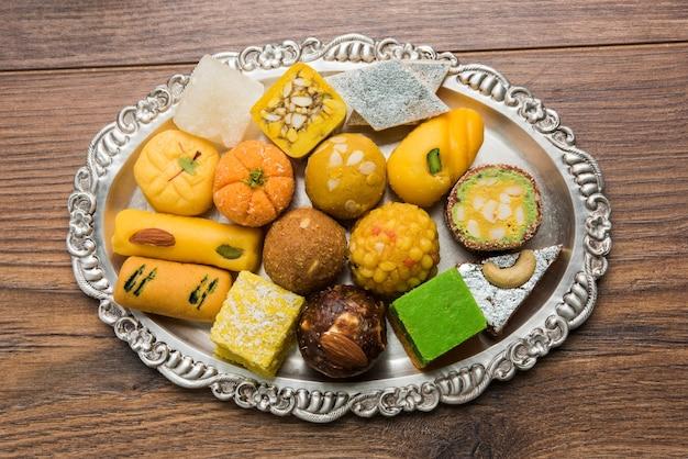 Indyjskie słodycze podawane w srebrnym lub drewnianym talerzu. odmiana peda, burfi, laddu w ozdobnym talerzu, selektywne skupienie