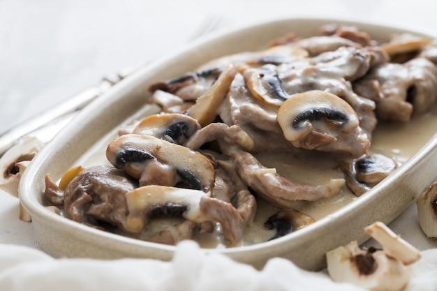 Indyk z pieczarkami i sosem na naczyniu na ceramice