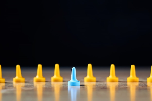 Indywidualność i przywództwo. niebieska postać wyróżnia się na tle żółtych postaci