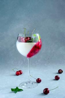 Indywidualny deser w kieliszku do wina z wiśniami. panna cotta z jagodami w szkle na szaro.