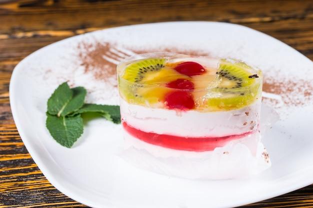 Indywidualny owalny kremowy mus jagodowy z owocami kiwi podany na talerzu na rustykalnym drewnianym stole na smaczny deser