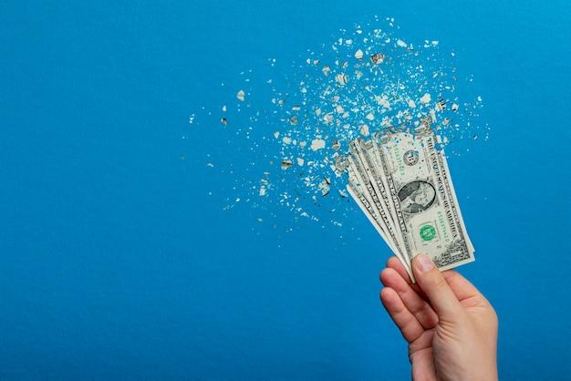 Inflacja, hiperinflacja dolara. baner z niebieskim tłem. jeden banknot dolarowy jest rozpylany w dłoni mężczyzny na niebieskim tle. koncepcja wzrostu cen.