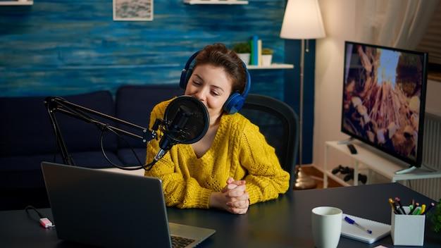 Influencer ustawia mikrofon i odpowiada na maile w słuchawkach podczas transmisji w domowym studiu. kreatywny program online produkcja internetowa podcast hostujący transmisję strumieniową na żywo