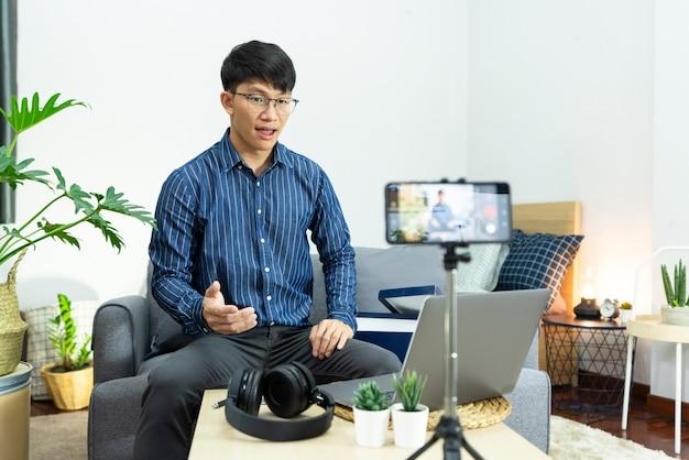 Influencer w mediach społecznościowych lub bloger prezentuje i recenzuje nagrania lub streaming vloga na temat produktu za pomocą smartfona na statywie