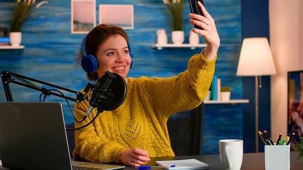 Influencerka w mediach społecznościowych używająca telefonu do nagrywania serii podcastów selfie dla publiczności